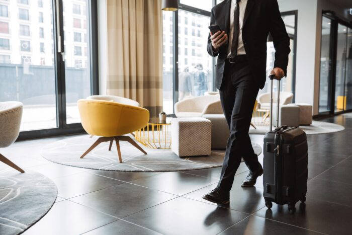 Business man traveling with suitcase and talking on looking at phone